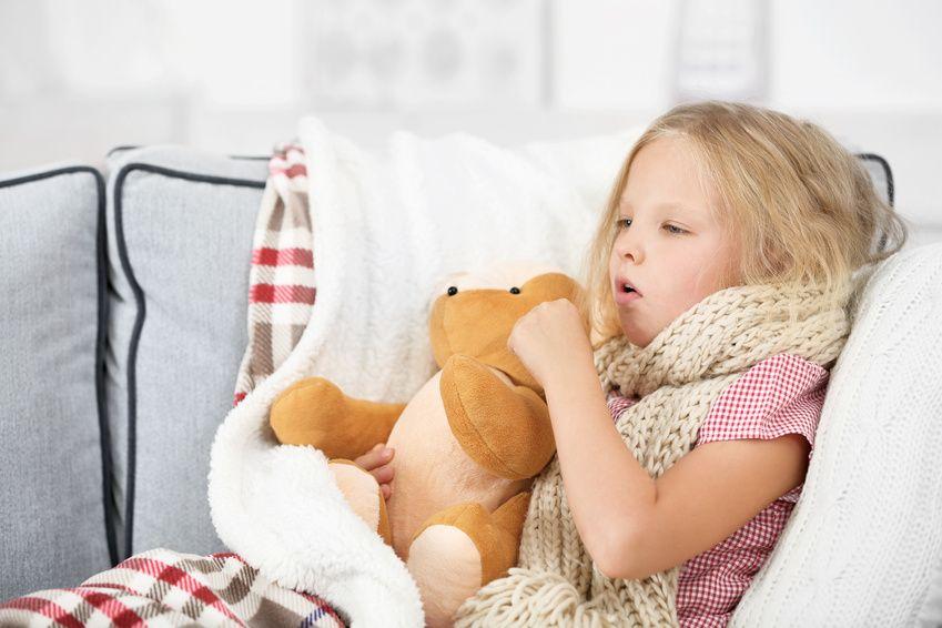 Kind krank auf dem Sofa mit Teddy und Schal