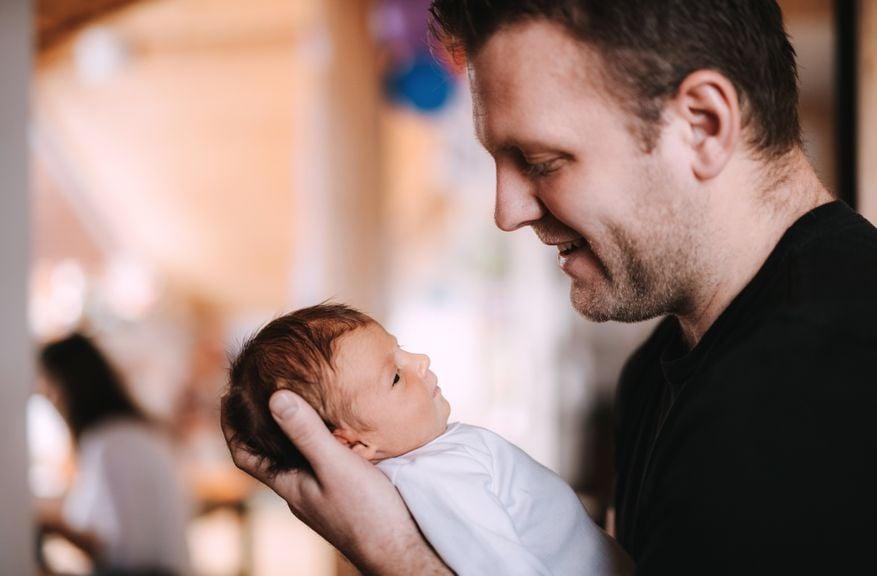 Vater lächelt sein Neugeborenes an