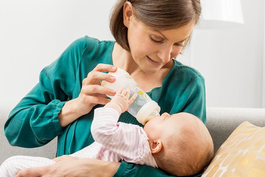 Mutter gibt ihrem Baby den Schoppen