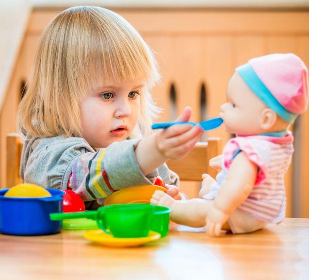 Mädchen füttert seine Puppe