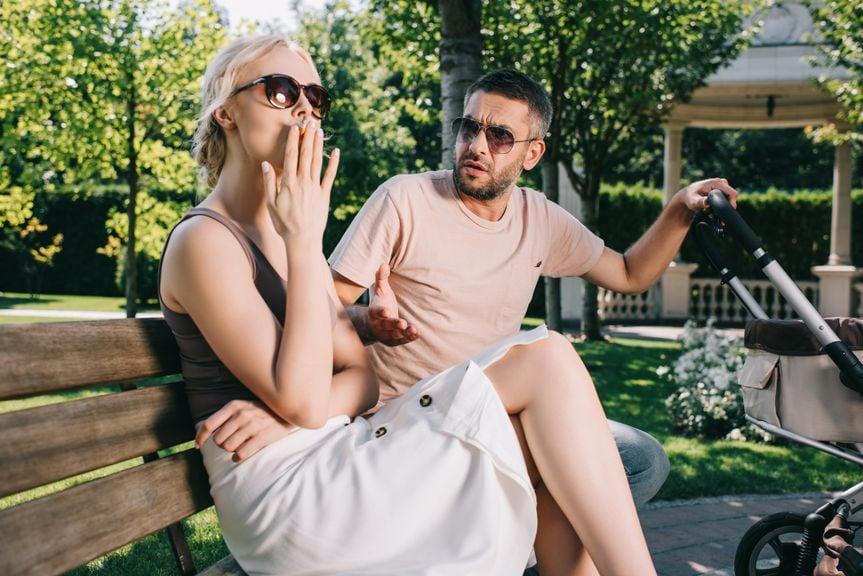 Paar mit Kinderwagen sitzt auf Parkbank, Frau raucht