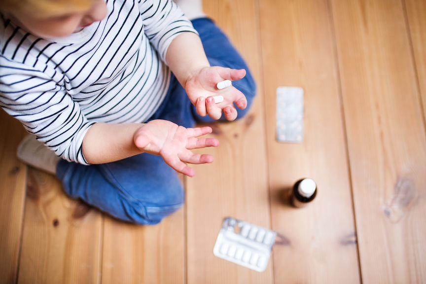 Kind hält Medikamente in der Hand