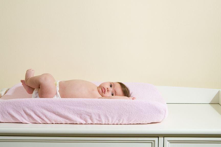 Baby liegt alleine auf dem Wickeltisch
