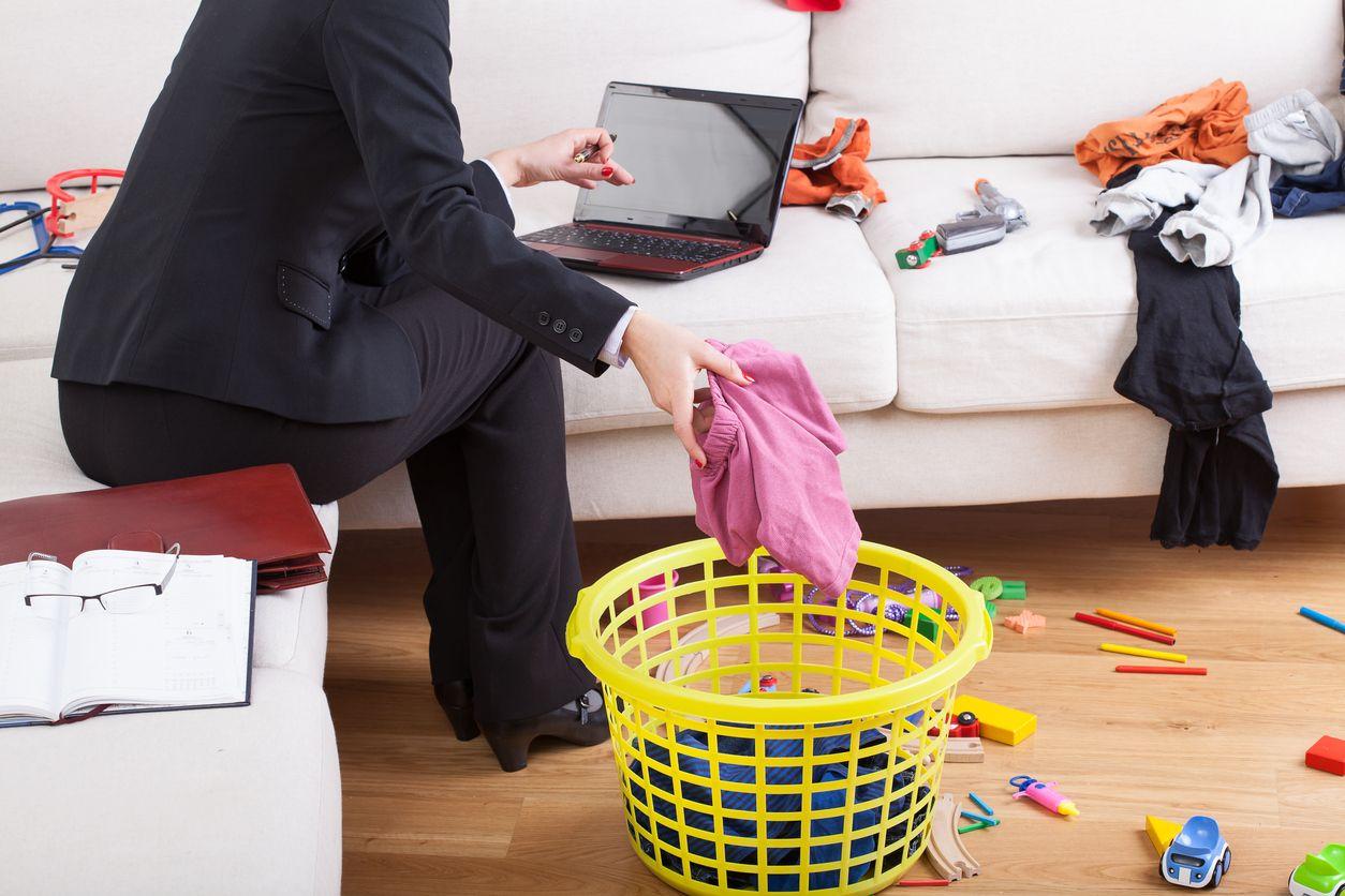 Frau sitzt auf dem Sofa, arbeitet am Laptop und legt ein Wäschestück in den Korb