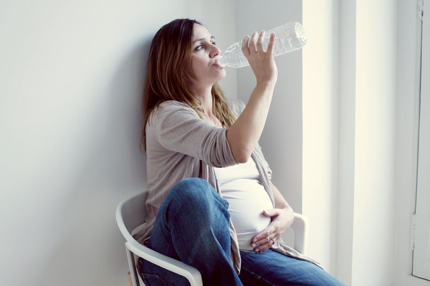 Schwangere trinkt aus Wasserflasche