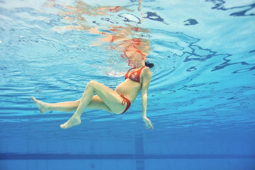 Schwangere schwimmt im Wasser