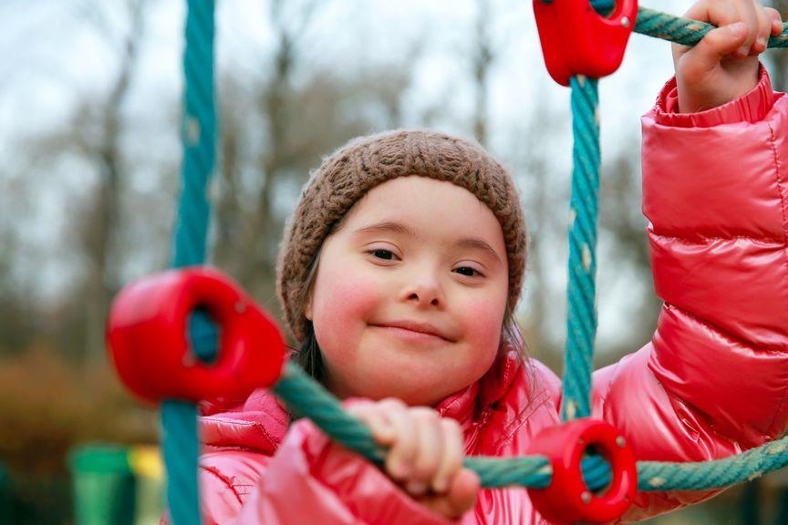 Mädchen mit Trisomie 21 auf dem Spielplatz