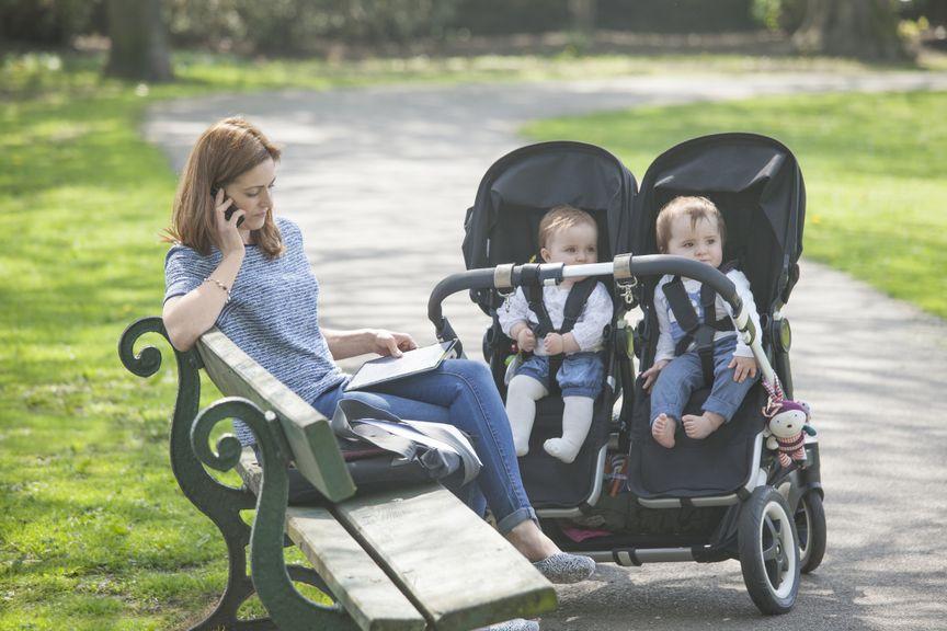 Mutter auf einer Parkbank mit Zwillingen im Buggy