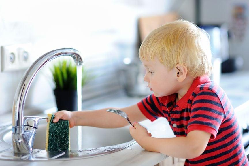 Kleiner Junge am Abwaschbecken, wäscht ab mit einem Schwamm