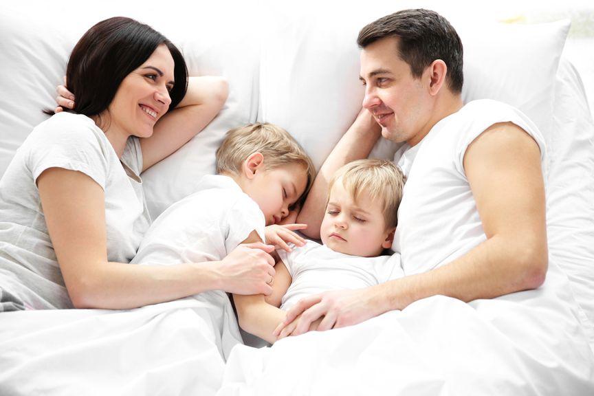 Familie mit zwei Kindern im Bett