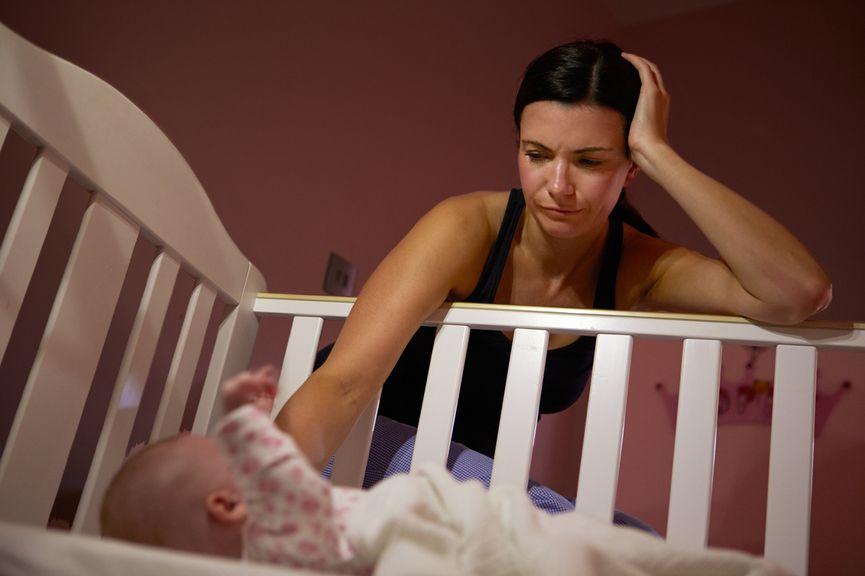 Mutter sitzt am Gitterbett, Baby wach